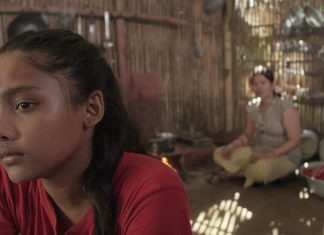 Ein hinduistisches Mädchen sitzt in einer Bambushütte, im Hintergrund unscharf die Mutter