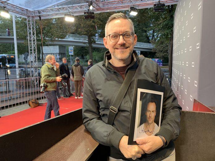 Autogrammjäger Carsten Werner mit einem signierten Bild am roten Teppich