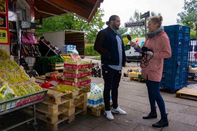 """FINK.HAMBURG Redakteurin Nina Maurer steht mit Ali Hakim, dem Regisseur des Films """"Bonnie & Bonnie"""", vor einem Kiosk und richtet ein Mikrofon auf ihn. Neben den beiden steht viel Obst und Gemüse auf Paletten."""