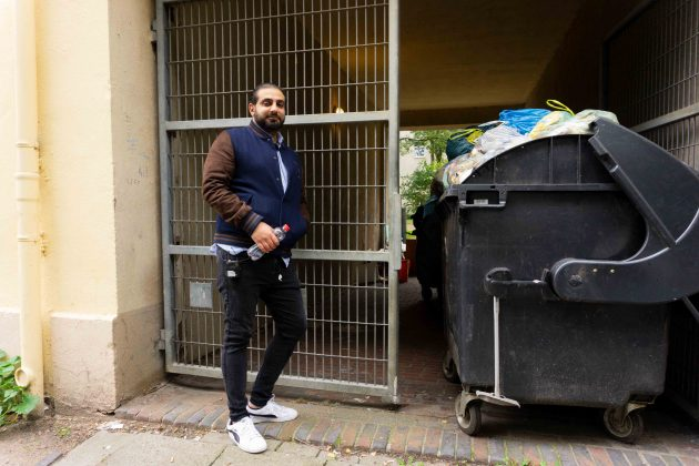 """Ali Hakim, der Regisseur des Films """"Bonnie &Bonnie"""", steht vor einer Toreinfahrt, in der Müllcontainer stehen, aus denen die Müllsäcke oben herausgucken."""