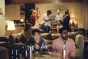 fünf Jugendliche auf einer Party im Wohnzimmer.