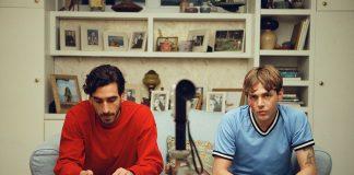 Matt und Max sitzen auf einem Sofa und schauen in die Kamera