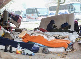 Ein mit Kapuze vermummter obdachloser Mann, der inmitten eines provisorischen Matratzenlagers unter der Brücke sitzt.