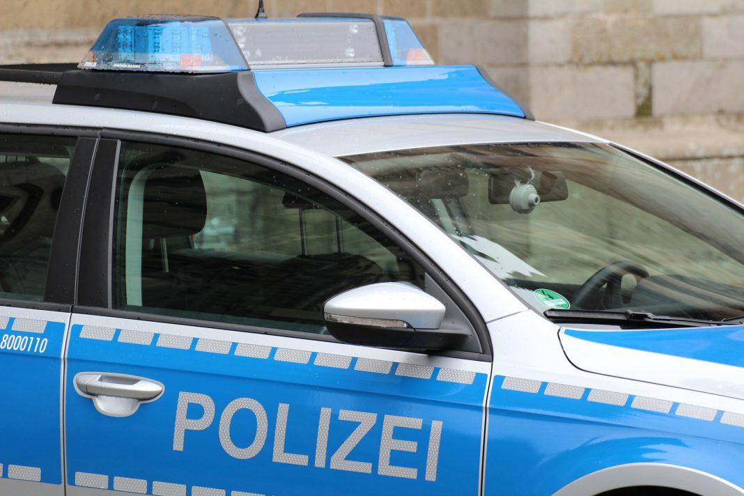 Ein Polizeiwagen, der vor einem Steinwand parkt.