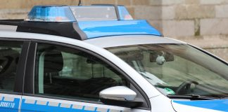 Ein Polizeiwagen, der vor einem Steinwand parkt.