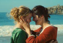 """Zwei Frauen umarmen sich am Meer. Still aus dem Film """"Portrait einer jungen Frau in Flammen""""."""