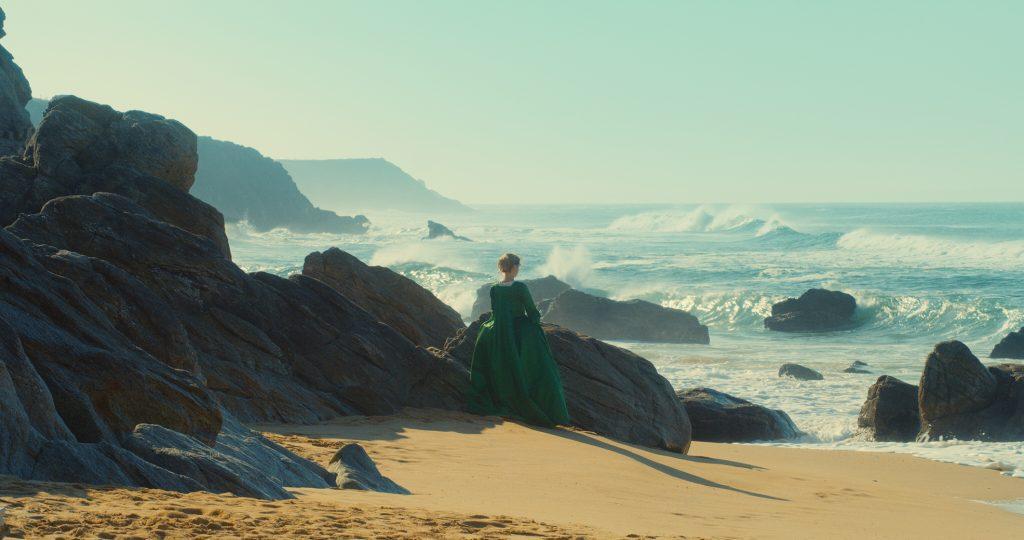 """Frau in langem, barocken Kleid steht am Strand. Filmstill aus """"Portrait einer jungen Frau in Flammen"""""""