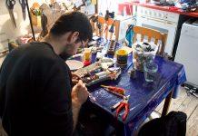 Mann repariert und schraubt an einem Draht. Auf seinem Tisch herrscht Chaos.