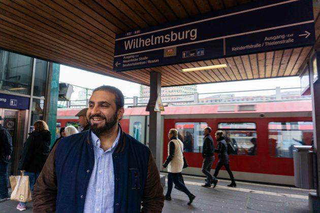 """Ali Hakim, der Regisseur des Films """"Bonnie & Bonnie"""" steht unter dem Schild der S-Bahn-Station Wilhelmsburg. Hinter ihm steht eine S-Bahn im Gleis."""