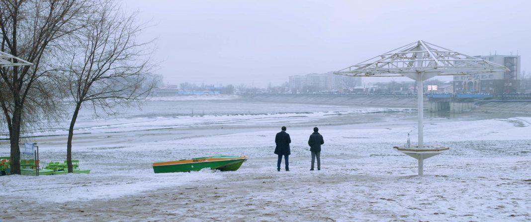 Zwei Männer sitzen am Strand in einem gestrandeten Boot und reden miteinander, während es schneit.