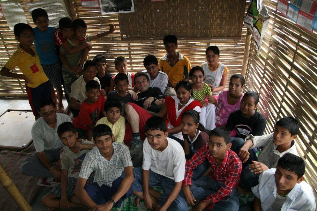 Aufnahme von oben einer Gruppe von sitzenden Kindern in einer Bambushütte.