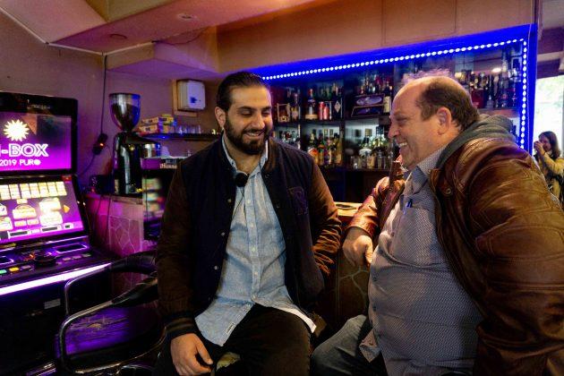 """Ali Hakim, der Regisseur des Films """"Bonnie & Bonnie"""", und der Besitzer der Sportbar Rexhep Ismaini sitzen am Tresen der Bar."""
