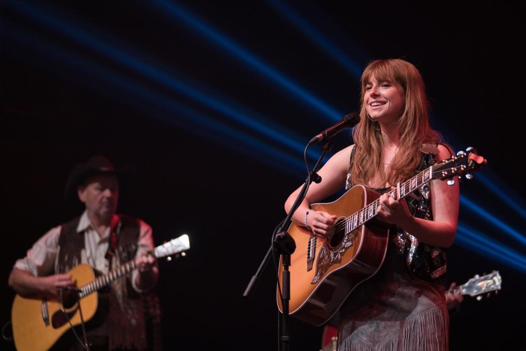 """Jessie Buckley spielt Rose-Lynn Harlan im Film """"Wild Rose"""". Sie steht auf einer Bühne und spielt Country-Musik."""