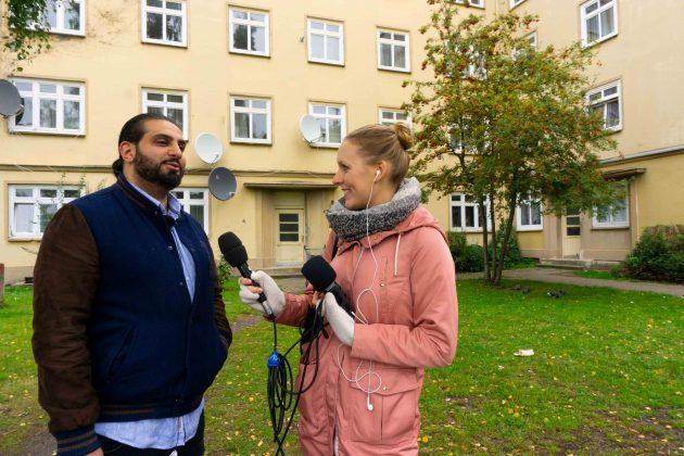 """FINK.HAMBURG Redakteurin Nina Maurer steht mit Ali Hakim, dem Regisseur des Films """"Bonnie & Bonnie"""", vor einem gelben Haus. Sie richtet ein Mikrofon auf Ali Hakim."""