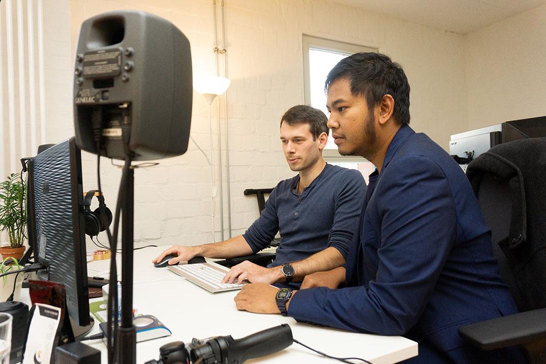 Zwei Männer sitzen an einem Schreibtisch und arbeiten an 3D-Sounds.