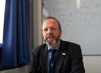 Portrait von Prof. Dr. Christoph Maas. Er sitzt in seinem Büro an einem Schreibtisch.