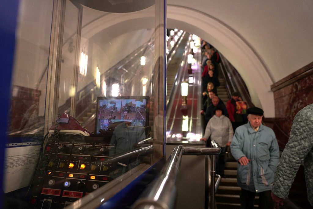 The escalator operators watch the people coming down to the subway.