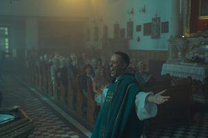 Daniel steht in der Kirche vor der Messe und lacht.