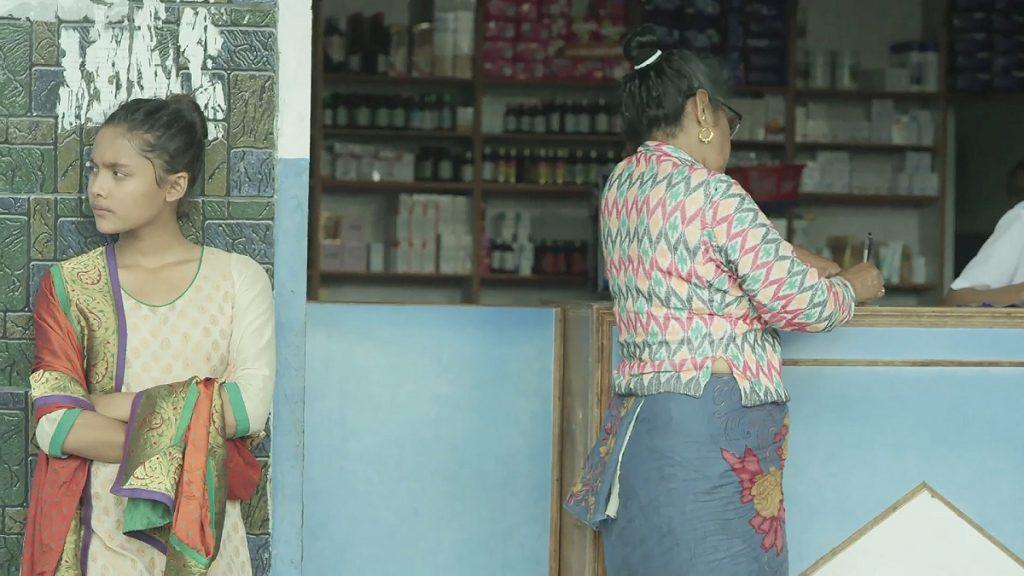 Nepalesisches Mädchen in hinduistischer Kleidung wartet an einem kleinen Geschäft in Asien auf ihre Großmutter