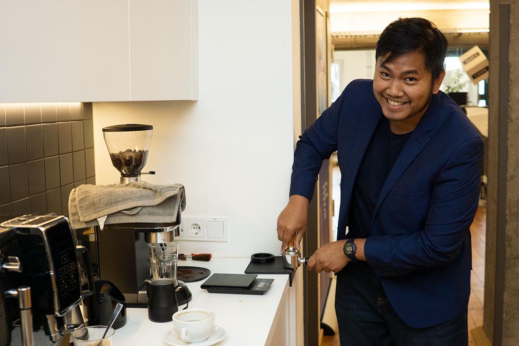Mann kocht Kaffee mit einer Espressomaschine. Im Hintergrund eine Büro.