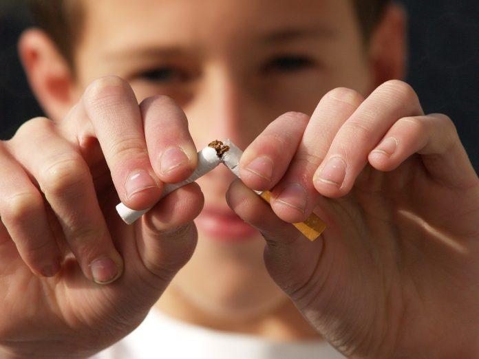 Kind zerbricht eine Zigarette