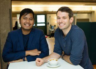 Zwei Männer stehen an einem Tisch. Sie haben ihr eigenes Start-Up für 3D-Sounds gegründet.