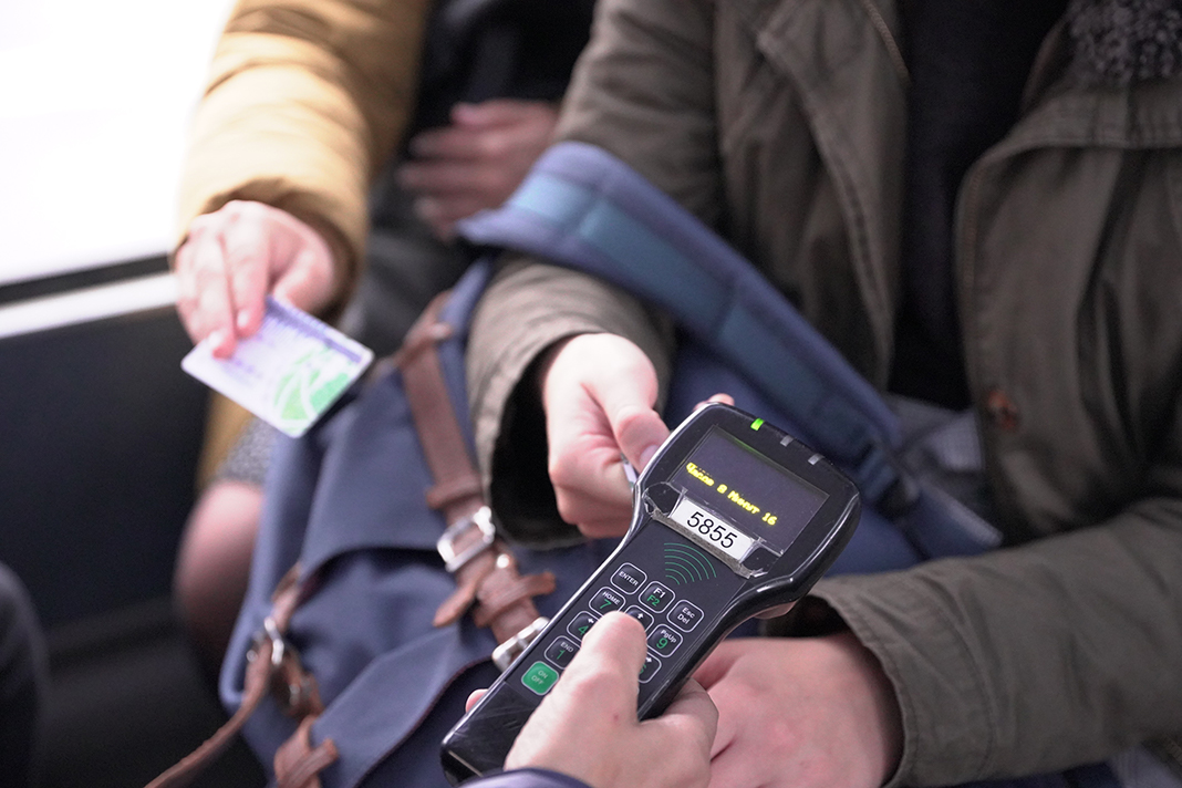 A Conductor is checking tickets with the tap device.