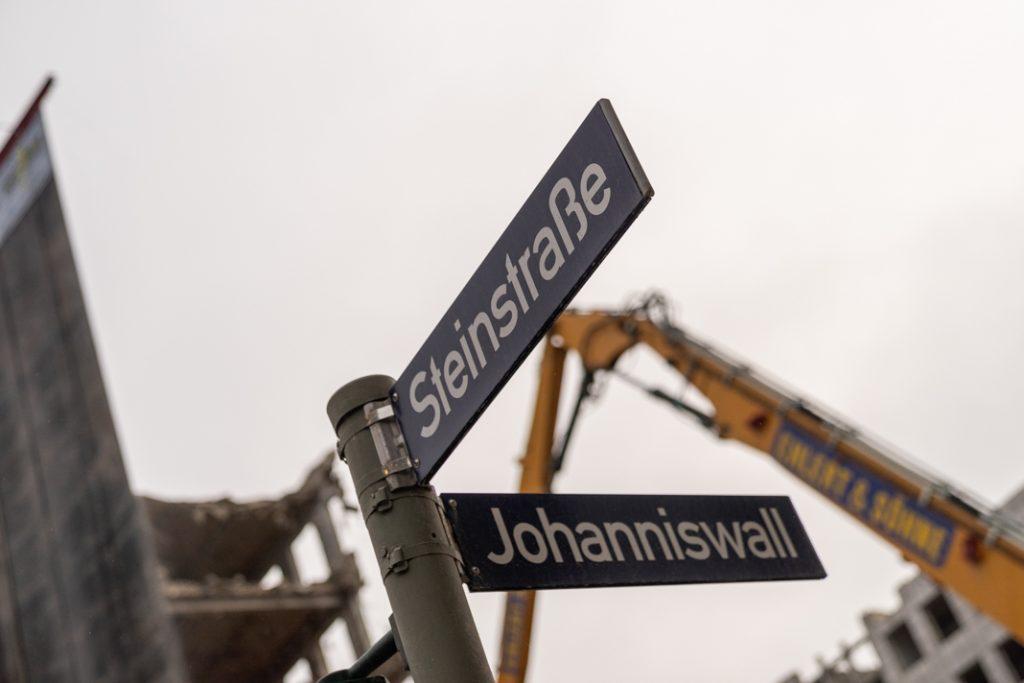Straßenschild Ecke Steinstraße/Johanniswall. Im Hintergrund: Abrissarbeiten am City-Hof. Foto: Benjamin Eckert