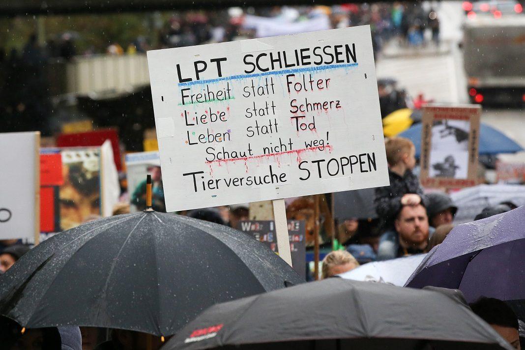 Ein Schild wird bei einer LPT-Demo in die Luft gehalten. Es fordert, das Labor zu schließen.