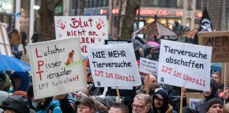 """Demonstrant*innen halten Schilder mit der Aufschrift """"Lutscher, Pisser, Tierquäler. LPT schließen"""", """"Nie mehr Tierversuche. LPT ist überall"""" und """"Tierversuche abschaffen."""