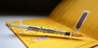 Eine Spritze die mit dem Namen des Vierfach-Grippeimpfstoff Influvac Tetra gekennzeichnet ist, liegt auf einem Impfpass.