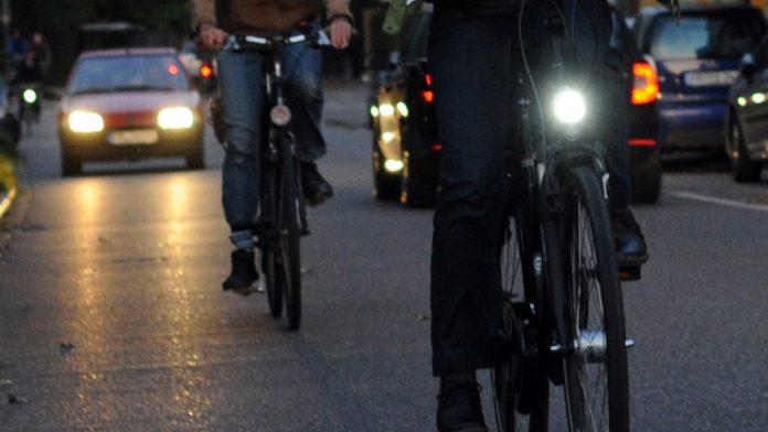 Zwei Fahrräder im dunklen, ein Fahrrad mit Licht, eines ohne.