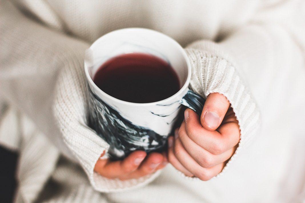 Zwei Hände halten eine Tasse mit einer Flüssigkeit.