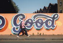 Ein Mann geht vor einer Wand mit Graffiti entlang.