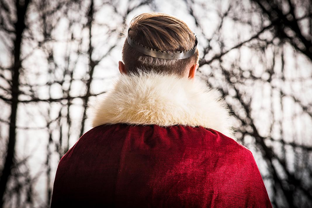 Mann mit kleiner Krone von hinten.