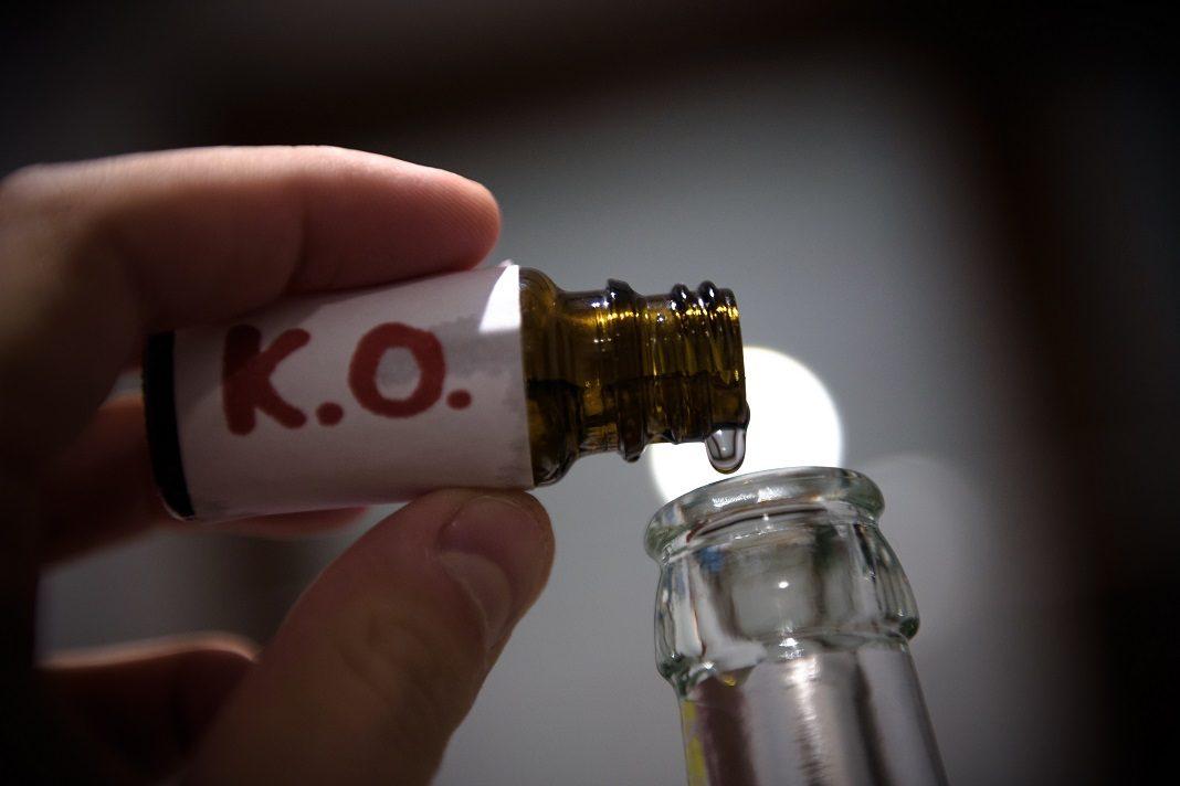 Ein Mann füllt in der gestellten Szene mehrere «K.O. Tropfen» in eine Bierflasche.