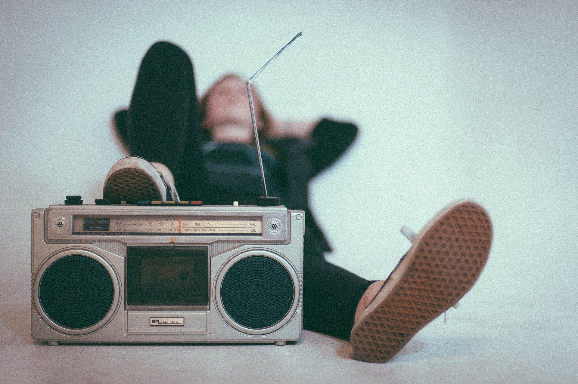 Ein Mann liegt auf dem Rücken und stellt seinen Fuß auf ein Radio mit Antenne