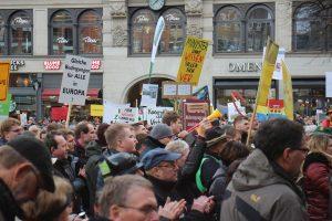 Männer und Frauen demonstrieren mit Schildern in Hamburgs Innenstadt