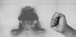 Stockfoto zum Thema Gewalt gegen Frauen. Frau sitzt Seelisch belastet zusammengekauert da. Eine Faust im Vordergrund droht der Frau