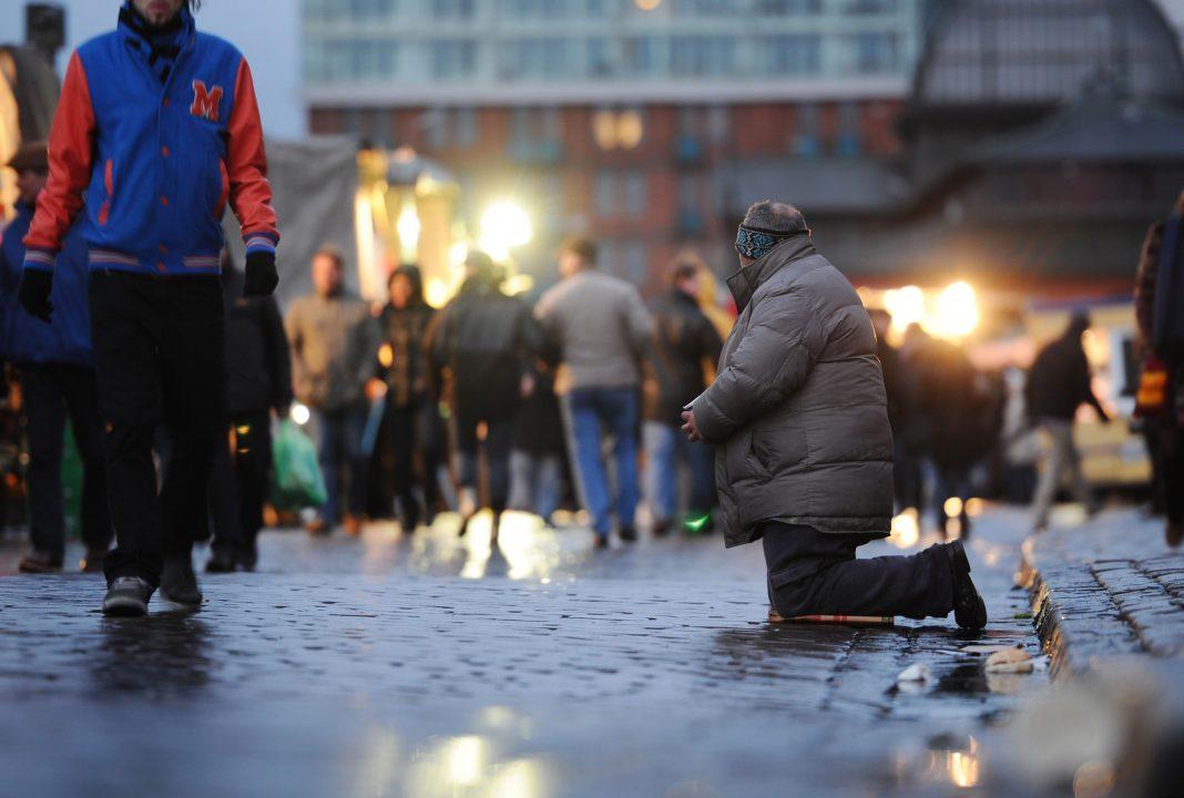 Ein Bettler kniet im Morgengrauen auf dem Fischmarkt am Hafen in Hamburg vor vorbeilaufenden Besuchern. Foto: Christian Charisius/dpa