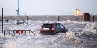 Ein Auto steht während des Sturmtiefs Wilfried bis über die Reifen im Wasser.
