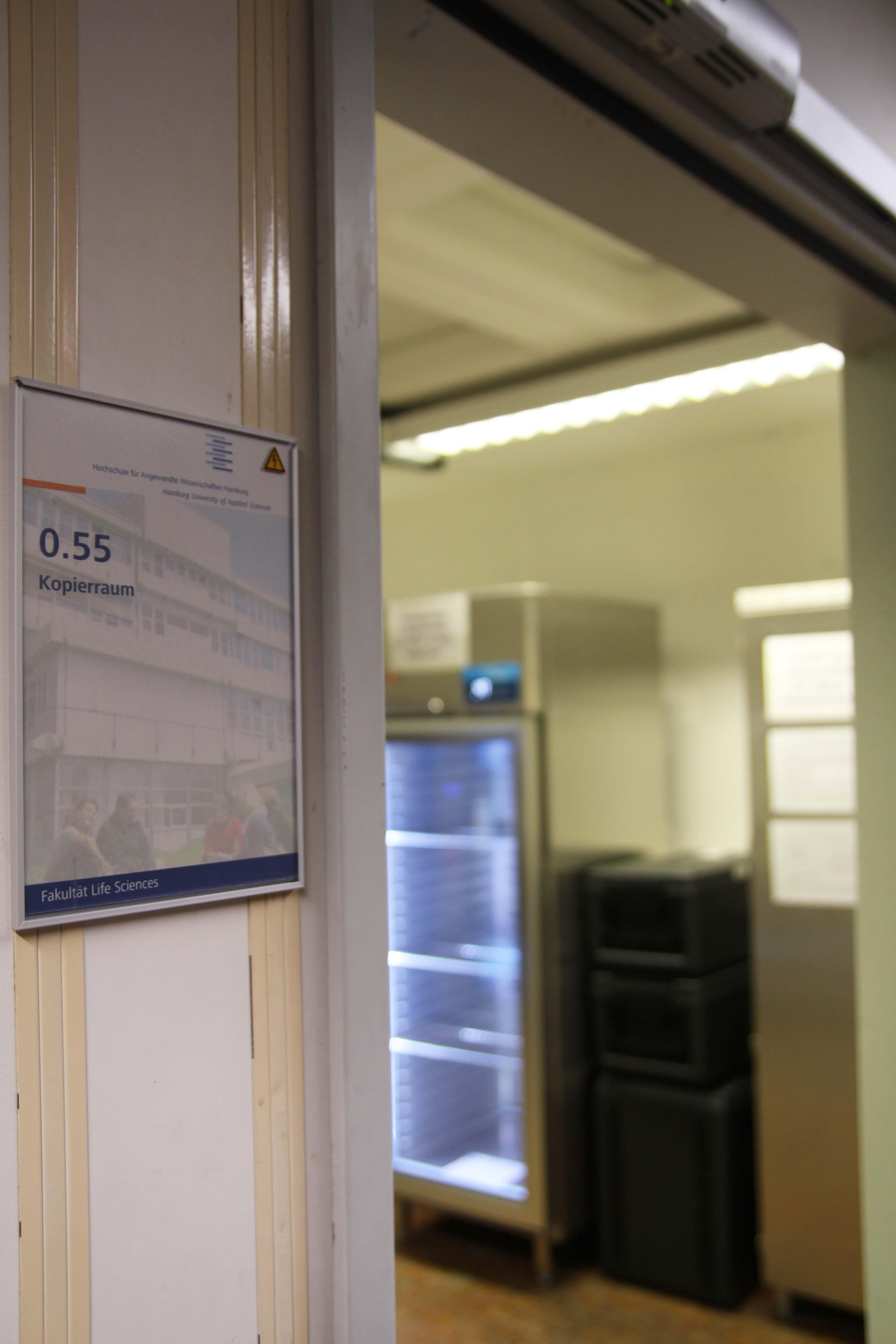 Im Vordergrund ein Türschild, auf dem Kopierraum steht. Im Hintergrund der Fair-Teiler.