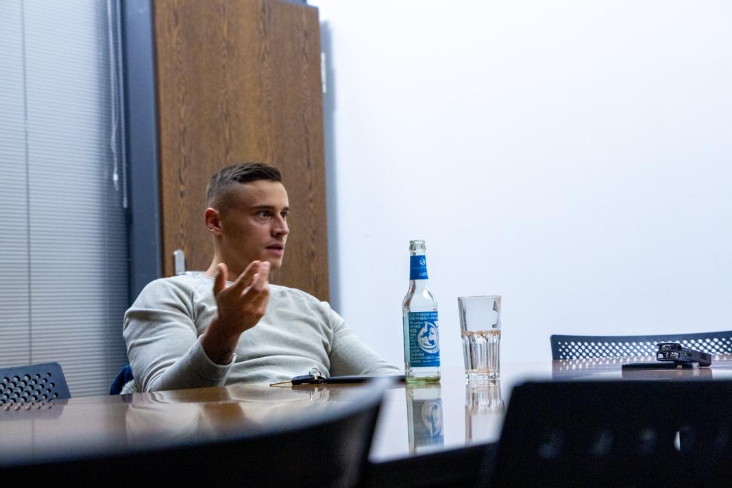 Disarstar sitzt an einem Tisch, redet und hat vor sich ein Wasser stehen. Foto: Dustin Balsing