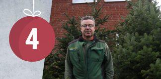 Kay Wortmann steht vor etwa zwei bis drei Meter hohen Weihnachtsbäumen in seinem Gartencenter.