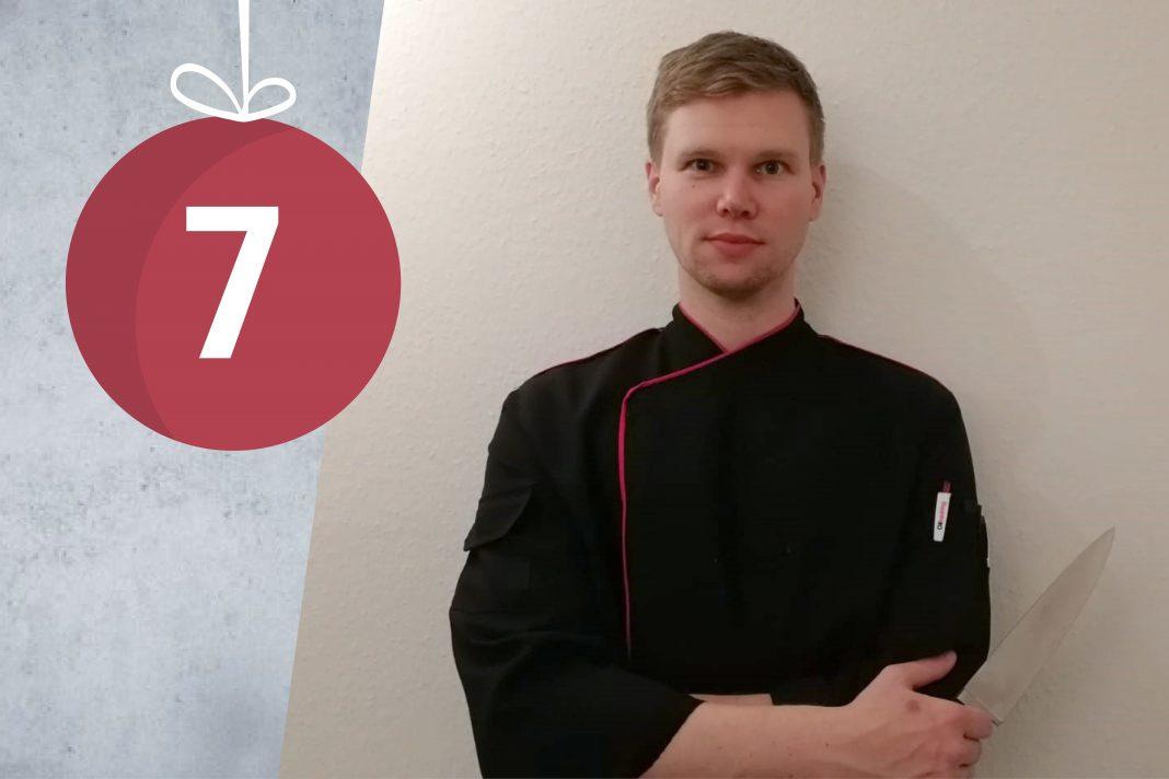 Kevin Schmidt steht mit einem Messer in der Hand vor einer weißen Wand.