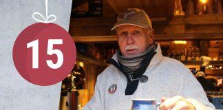 Ein älterer Herr mit Kappe hält einen Becher Glühwein in die Kamera.
