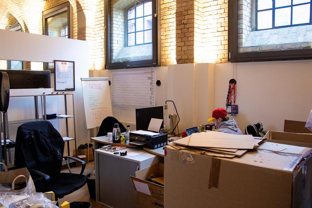 Mölli sitzt am Schreibtisch es alten Büros, versteckt hinter einem großen Karton.