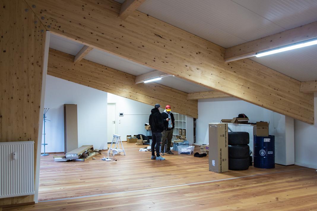 Timo und Mölli stehen unter einer Dachschräge in ihrem neuen Büro. Um sie herum Kartons und Verpackungen.