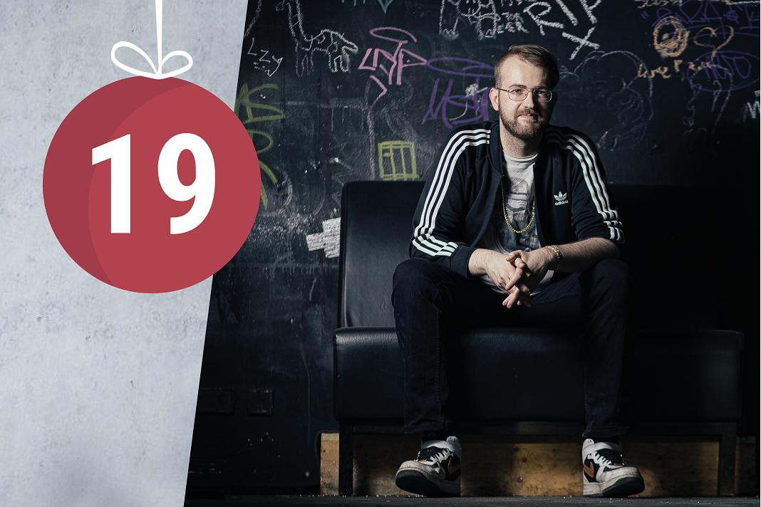Tobias Hacker sitzt auf einer Bank und lächelt.