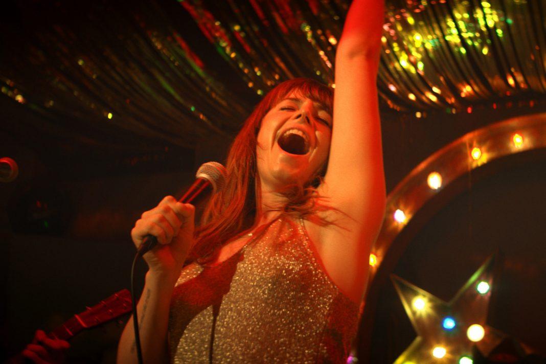 Protagonistin Rose (Jessie Buckley) singt auf der Bühne einer Country-Bar in Glasgow. Film: Wild Rose von Tom Harper.